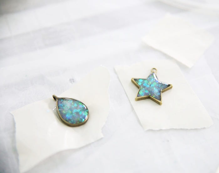 two bronze pendant necklaces filled with glitter epoxy resin jewelry teardrop and star shapes