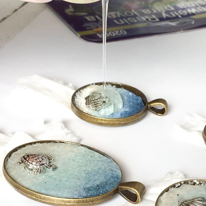 two bronze vintage necklace pendants epoxy resin jewelry small silver figurines inside being filled with resin