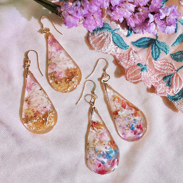 two pairs of earrings in raindrop form dried flowers on the inside in different colors resin jewelry placed on white silk cloth