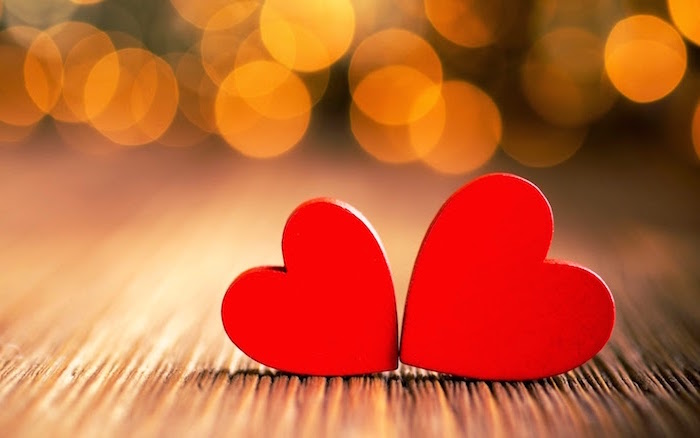 two red hearts placed next to each other placed on wooden surface valentines background blurred lights in the background