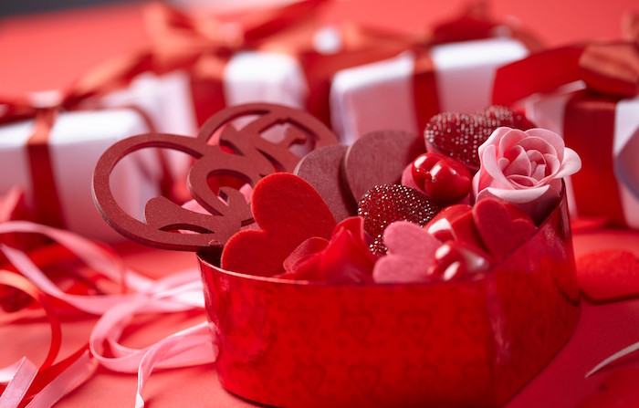 valentines background close up photo of red heart shaped box filled with small felt hearts candy and pink red roses