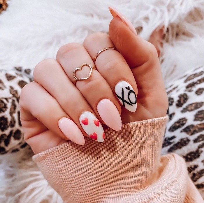 valentine's day acrylic nails white nail polish xo written on index finger red hearts on middle finger