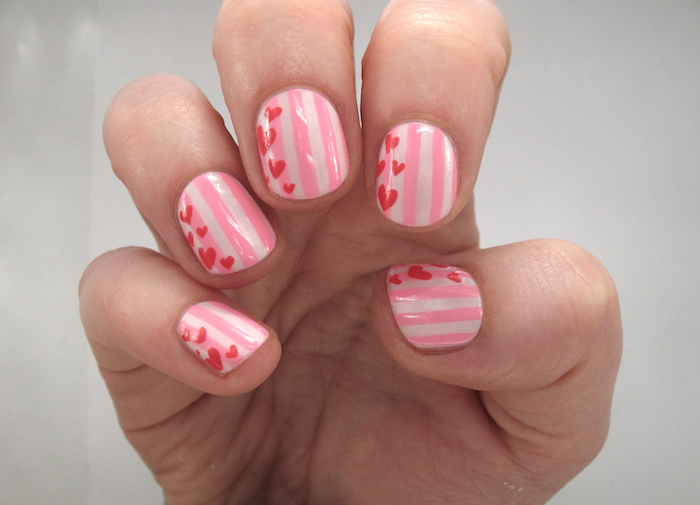 valentines day nail ideas stripes in different shades of pink on short squoval nails red hearts drawn on each nail