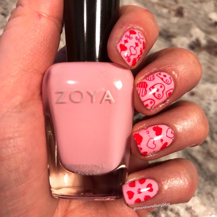 valentines day nails short squoval nails with pink nail polish red hearts in different shapes drawn on them