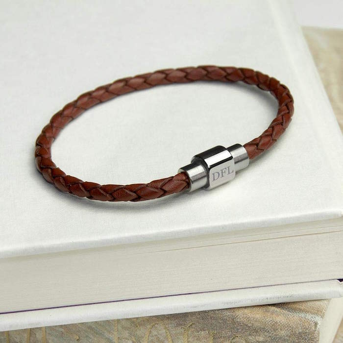 valentines gifts for him brown leather bracelet with personalised clip with three initials placed on white table