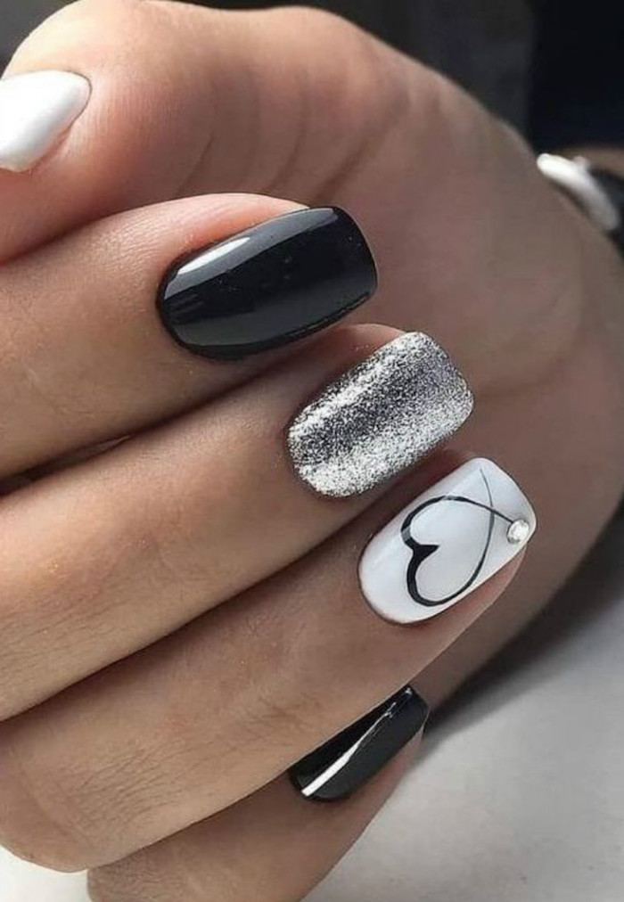 valentines nails black white and silver glitter nail polish on short squoval nails black heart drawn on ring finger