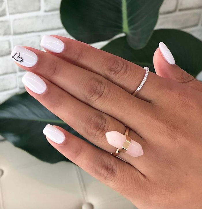 white nail polish on medium length squoval nails valentines day nails 2021 black heart outline on middle finger