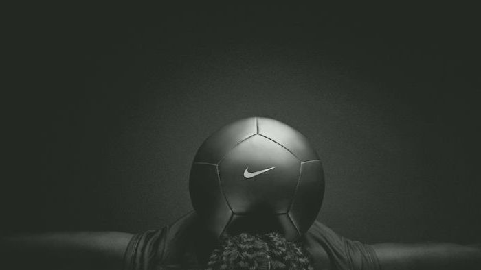 white nike logo on black football standing on the neck of person nike wallpaper black and white wallpaper
