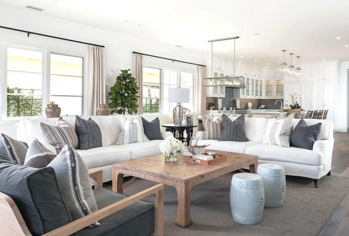 white sofas with gray white throw pillows gray armchair large wooden coffee table coastal home decor