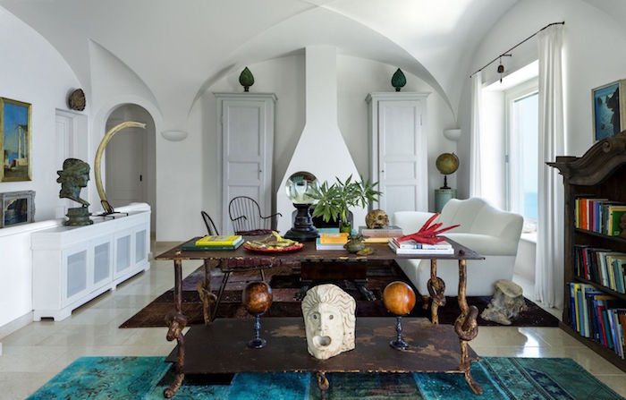 white walls and cathedral ceiling beach themed decor white sofa in front of fireplace vintage wooden table and bookshelf