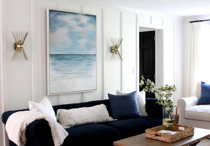 white walls ocean painting above blue velvet sofa beach bathroom decor wooden coffee table white armchair
