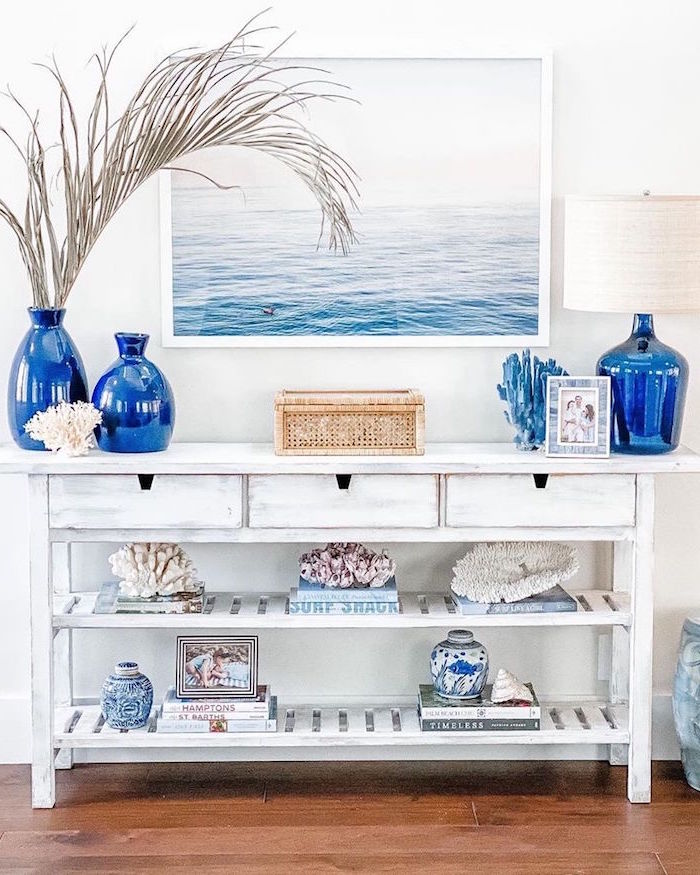 white wooden table with blue vases books and corals on it coastal living room framed ocean painting above it