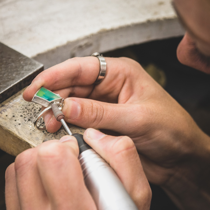 woman shaping a silver ring with turquoise resin inside resin earrings wearing silver ring on her index finger
