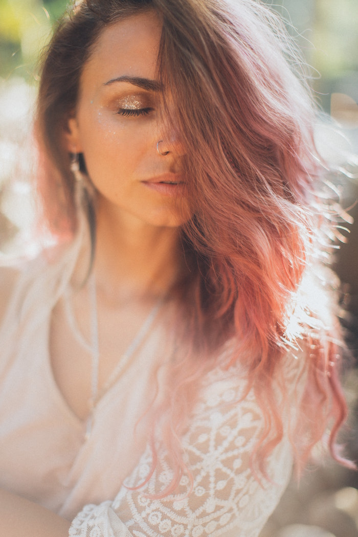 woman with medium length wavy hair in pink color keep your hair healthy wearing white lacy top glitter eyeshadow