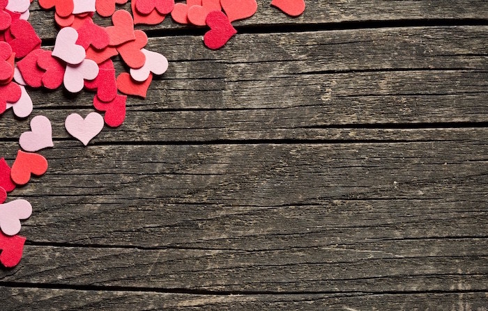 wooden background when is valentines day lots of small hearts in one of the corners in different shades of pink and red