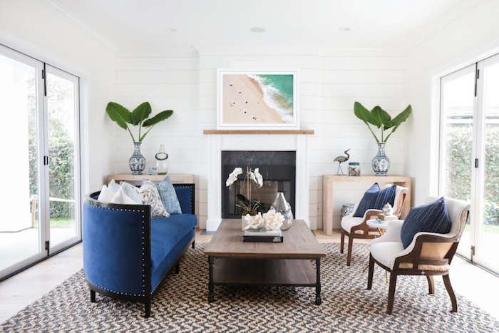 wooden coffee table blue velvet sofa white armchairs in front of fireplace coastal decorating ideas black and white carpet