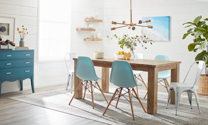 wooden dining table blue and white chairs around it on gray carpet on wooden floor coastal decorating ideas white shiplap walls
