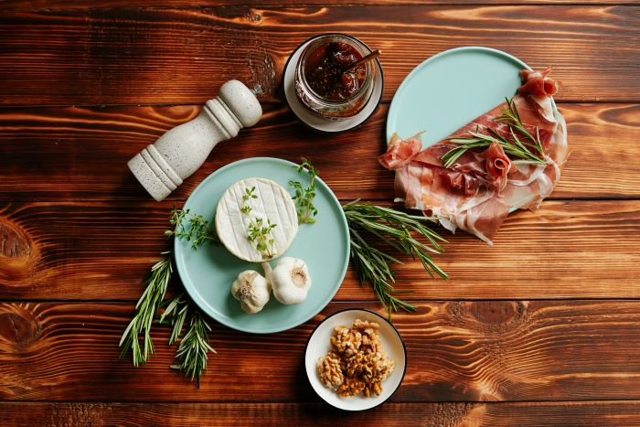 appetizer recipes ingredients brie prosciutto garlic jam rosemary walnuts spread on wooden surface