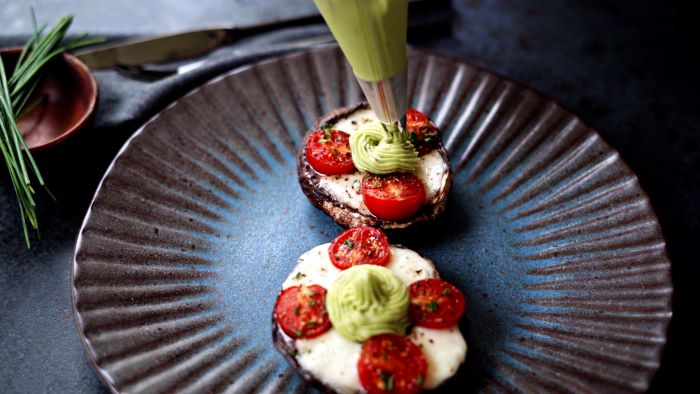 avocado mixture added to stuffed mushrooms with piping bag easy appetizers finger foods placed on ceramic plate