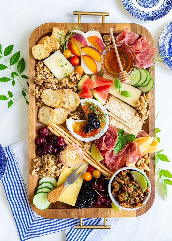 baked brie in the middle charcuterie board cheese meats fruits bread nuts on wooden tray