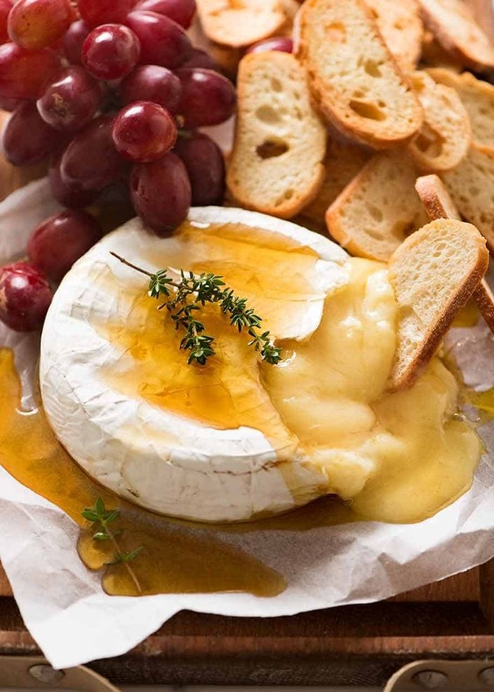 baked brie with honey and thyme charcuterie board bread and grapes on the side