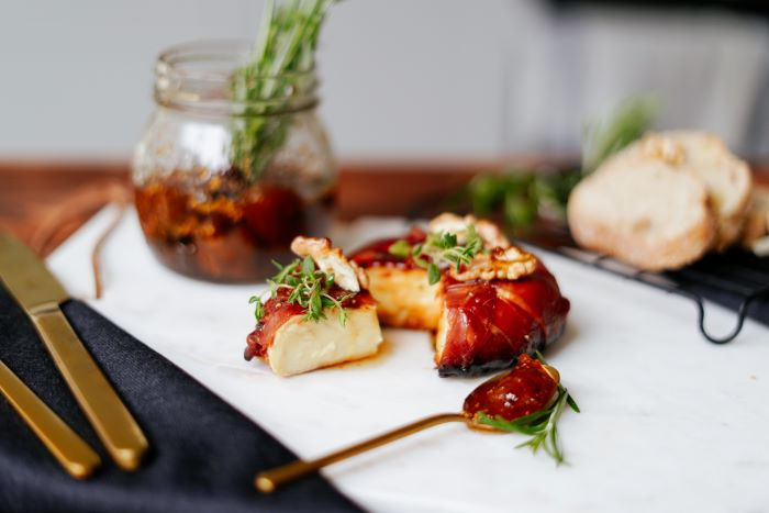 baked brie wrapped in prosciutto appetizer recipes drizzled with jam garnished with rosemary walnuts
