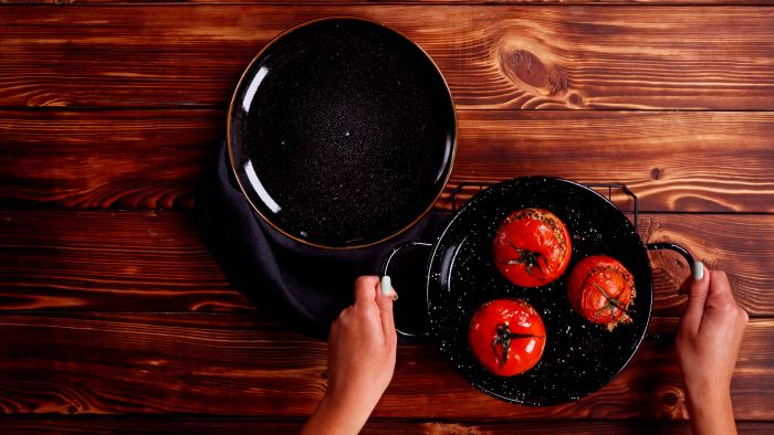 baked stuffed tomatoes in black baking dish finger food appetizers black plate placed on wooden surface
