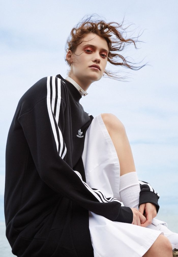 black adidas oversized sweatshirt white pants worn by woman with curly hair streetwear style