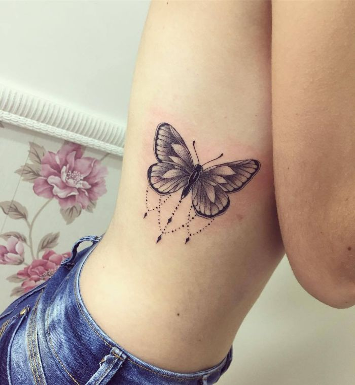 black and white butterfly tattoo on the side of the rib cage simple butterfly tattoo on woman wearing jeans