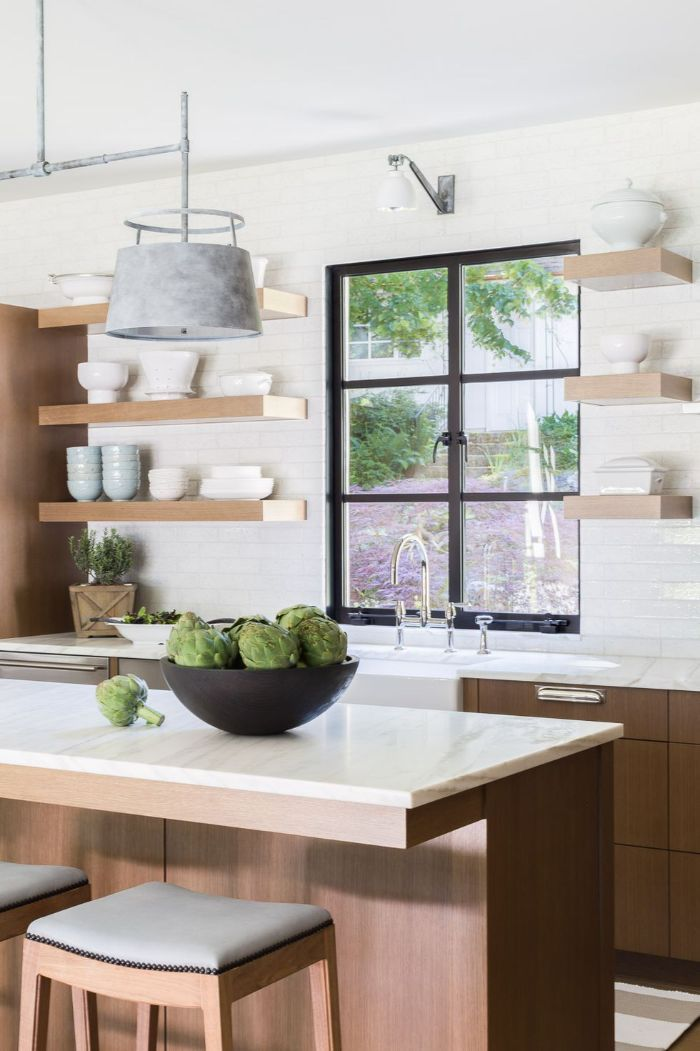 black bowl on wooden kitchen island wood floating shelves kitchen wooden cabinets white countertops tiled white backdrop