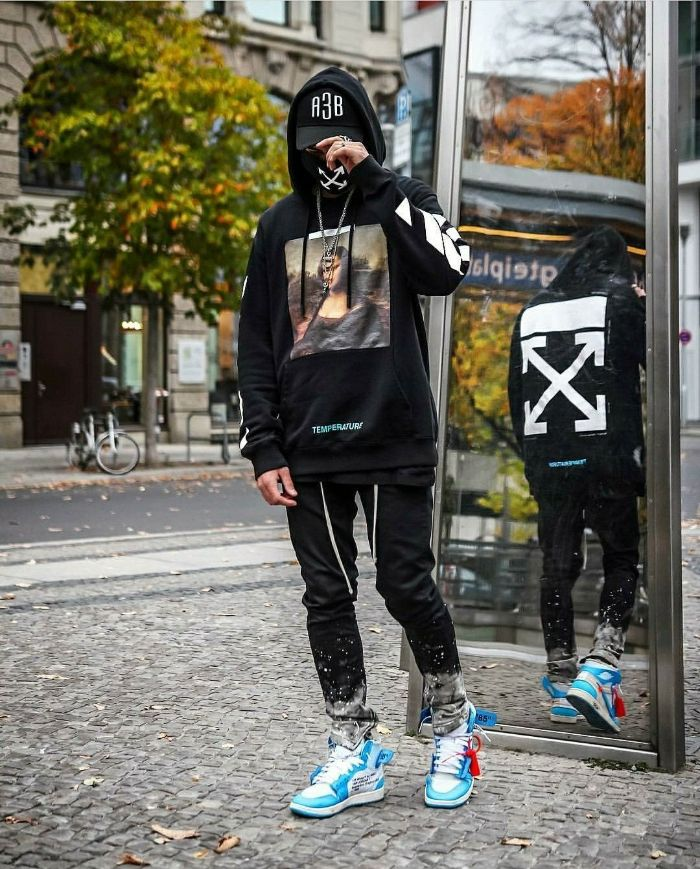black hoodie and jeans worn by man on the street with blue and white sneakers streetwear outfits off white