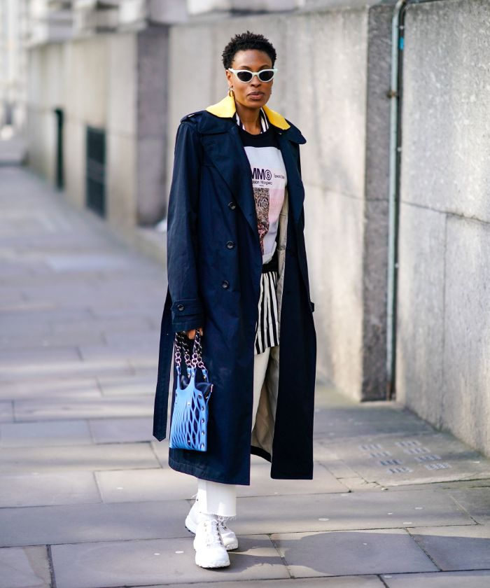 black long coat white pants white and black blouse mens streetwear worn by woman standing on the sidewalk