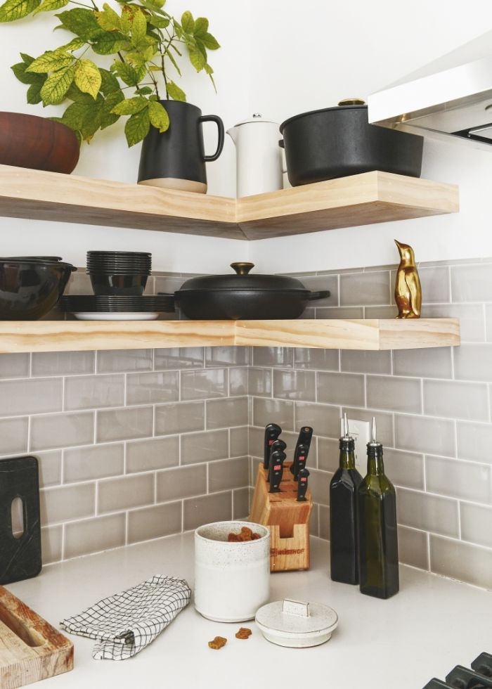 black pots and plates on wooden corner shelves floating kitchen shelves gray subway tiles backdrop white countertop