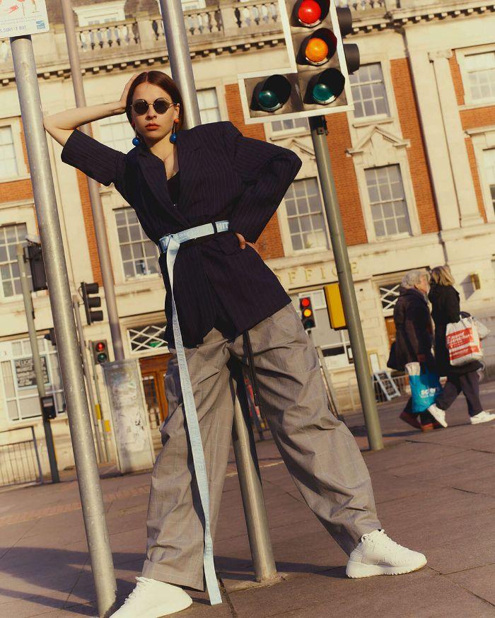 black wrap around blazer gray oversized pants white sneakers worn by woman mens streetwear standing on sidewalk