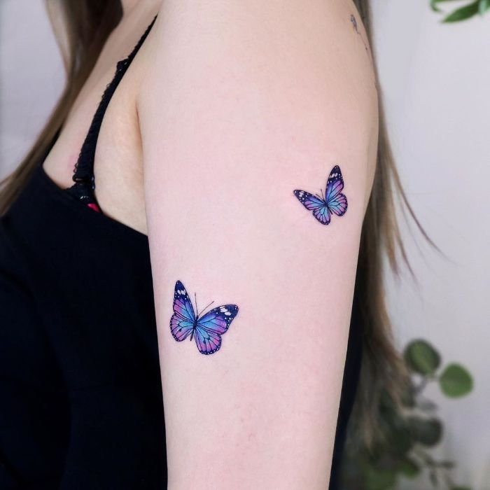 blue and purple watercolor two butterflies on the side of the arm butterfly tattoos on shoulder
