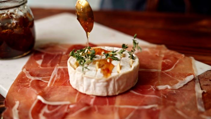 brie cheese placed on prosciutto with garlic and rosemary finger foods for party jam drizzled over it