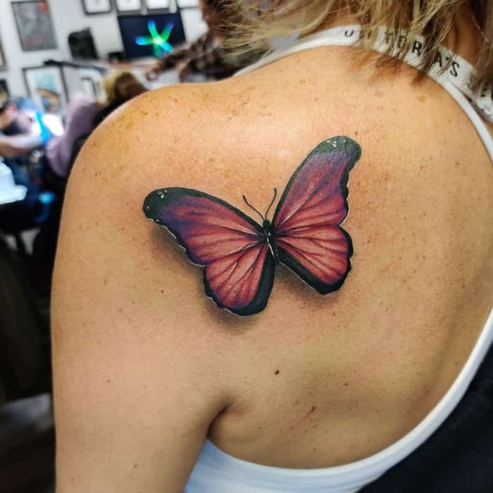 butterfly hand tattoo colored butterfly in orange and purple back of shoulder tattoo