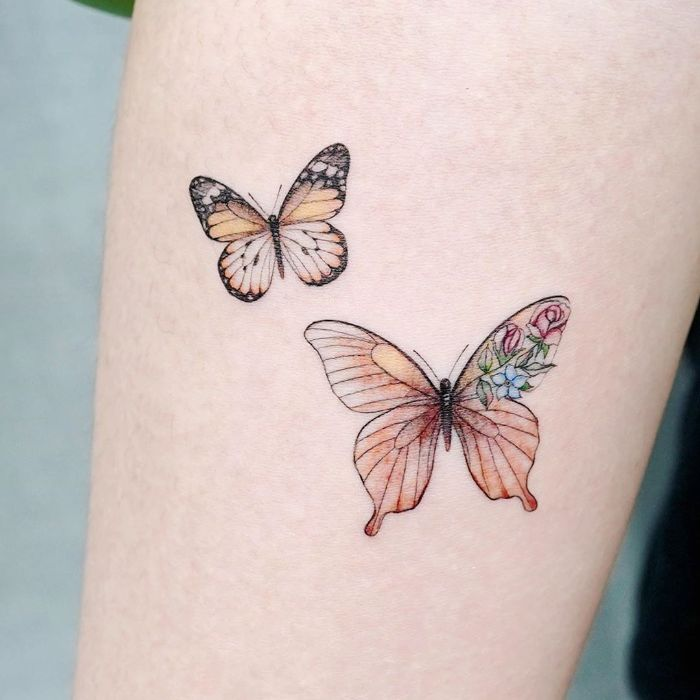 butterfly tattoo meaning two colored butterflies with flowers forearm tattoo