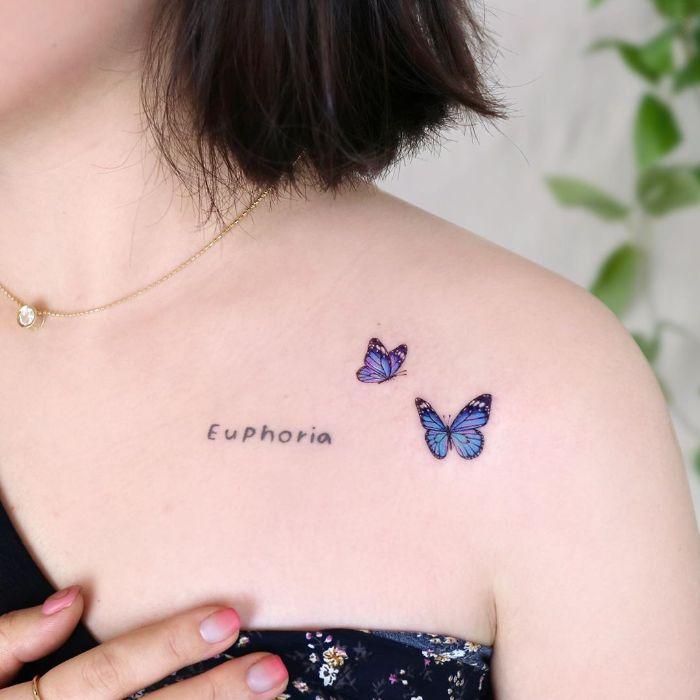 butterfly tattoo two blue butterflies in flight euphoria written next to them shoulder tattoo