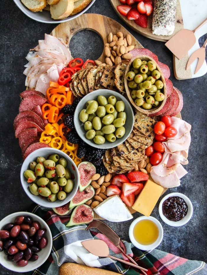 charcuterie board cheese pickled olives in bowls with crackers meats cheeses veggies and fruits