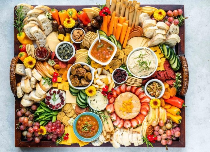 charcuterie board ideas large wooden tray filled with different types of cheese meat fruits veggies jams