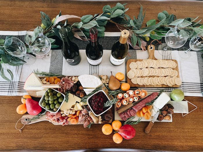 charcuterie board with meat cheese fruits crackers three wine bottles and wine glasses next to it