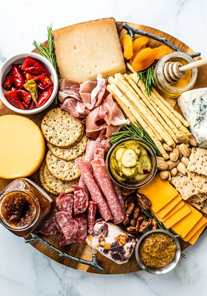 charcuterie platter with different types of meat cheese crackers veggies on round wooden tray