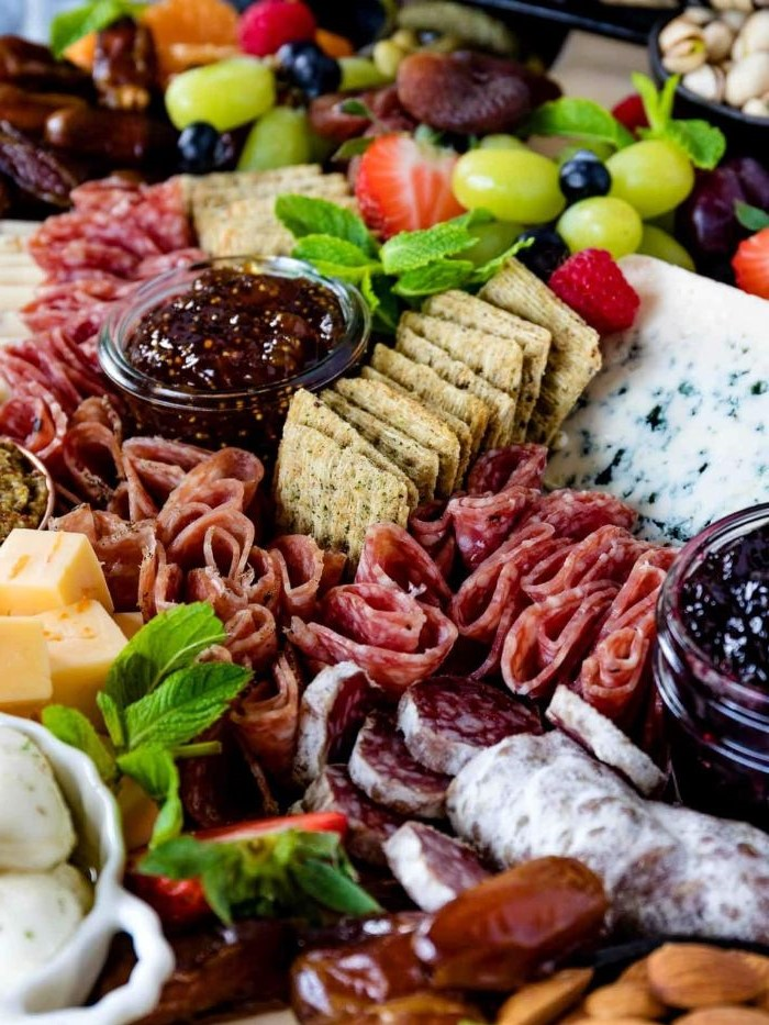 cheese board ideas crackers different types of meat small glass bowls filled with jam arranged together