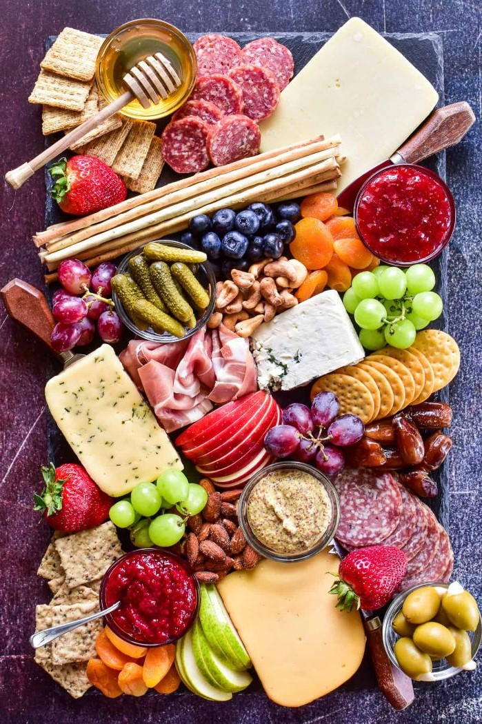 cheeses crackers meats pickles condiments fruits arranged on black stone board charcuterie platter