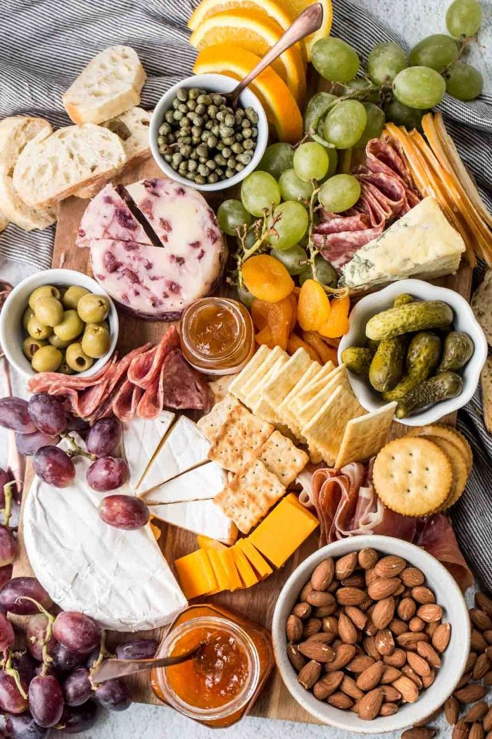 cheeses meats bread crackers grapes pickles olives nuts arranged on wooden board cheese board ideas