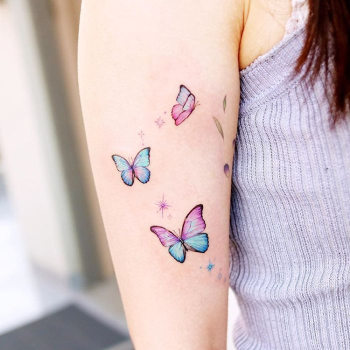 colored butterflies in purple and blue stars around them butterfly tattoo on arm three butterflies arm tattoo