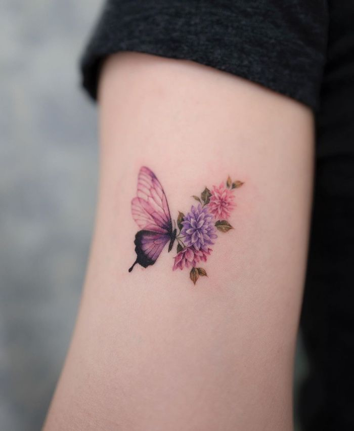 colored butterfly tattoo inside the arm small butterfly tattoo half purple half flowers in pink and purple