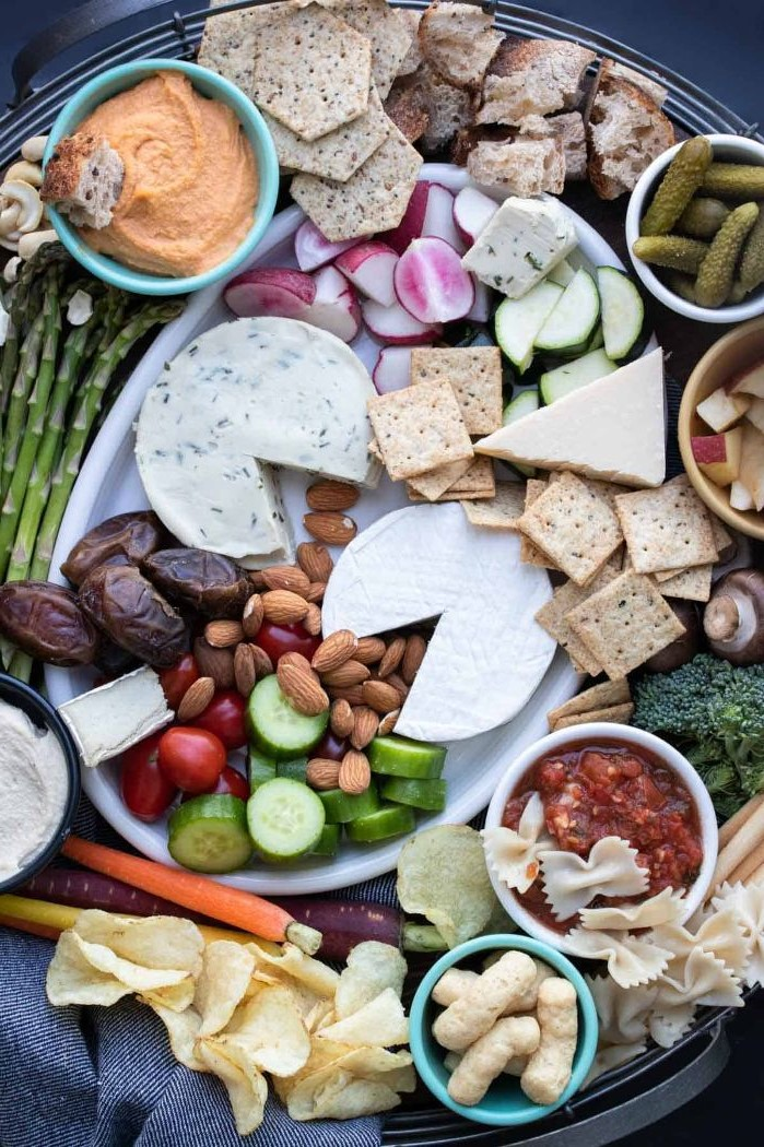 crackers hummus pickles cheeses vegan platter what is charcuterie nuts veggies on round tray