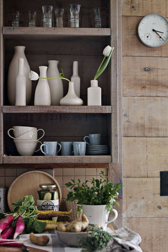 dark wooden backdrop open kitchen cabinets made of wood with glasses mugs and vases